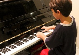 Boy playing piano is in the public domain.
